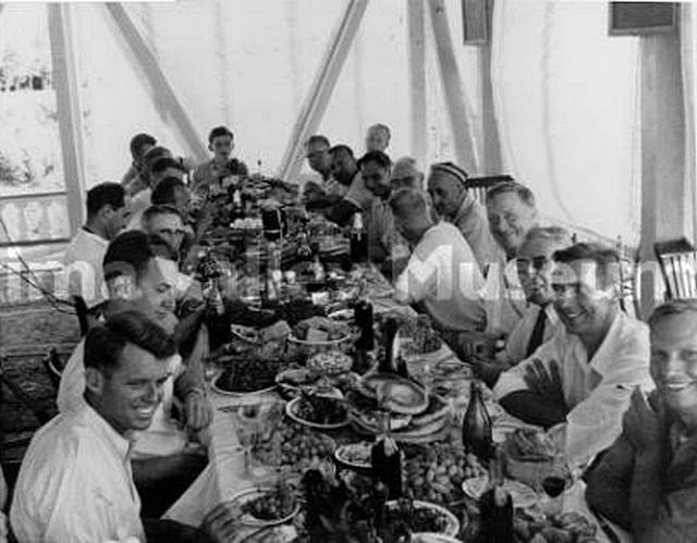Douglas with Robert Kennedy and others enjoy a traditional Uzbck feast while visiting a collective farm near Tashkent in the Soviet Union. 1955.